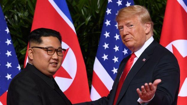 Donald Trump (R) gestures as he meets with North Korea's leader Kim Jong Un (L)