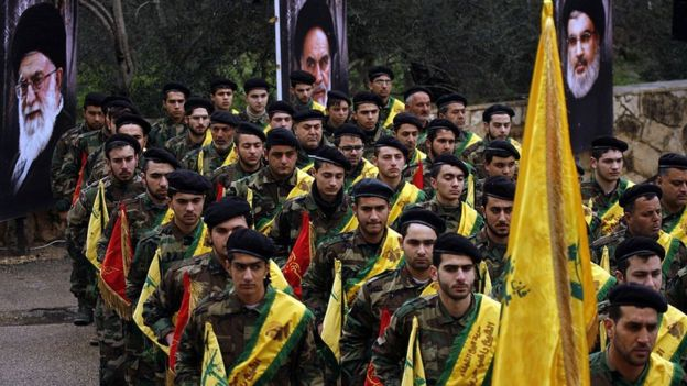 Hezbollah fighters march near portraits of Iranian and Hezbollah leaders (file photo)