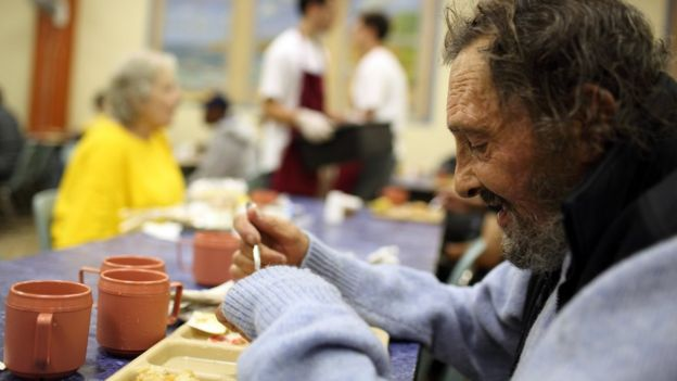 A homeless man eats in a soup kitchen in San Francisco