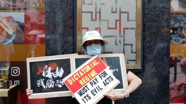 这名示威者举起的标语称,独裁政权要为邪恶的行为付出代价。