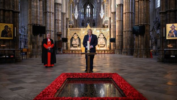 The Dean of Westminster, the Very Reverend Dr David Hoyle (left) looks on as Prime Minister Boris Johnson lights a candle at the Grave of the Unknown Warrior in Westminster Abbey in London