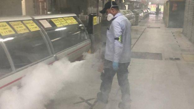 A man disinfects stalls at Plaza Minorista