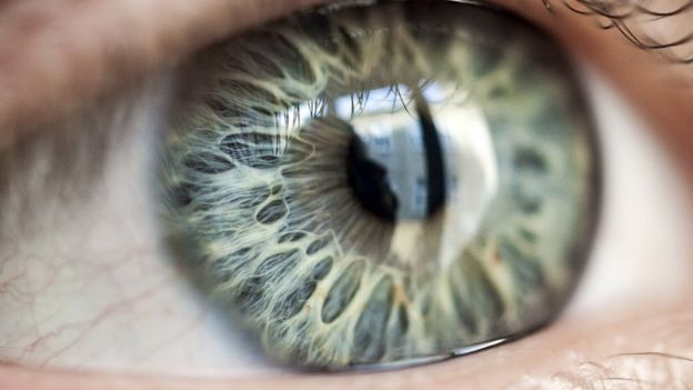 Ojo de cerca en el que se ve la reflexión de una persona frente a una ventana