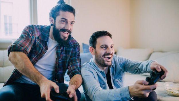 Dos hombres jóvenes jugando videojuegos.