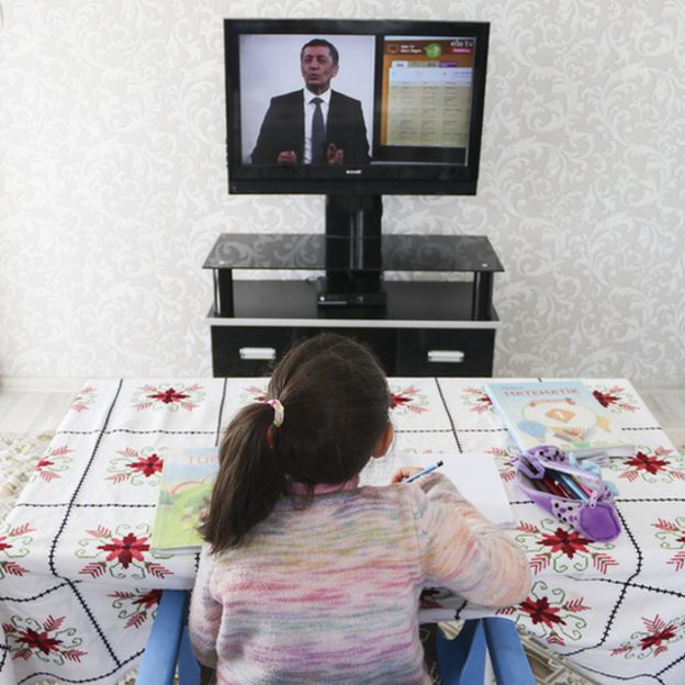 Niña mirando televisión educativa.