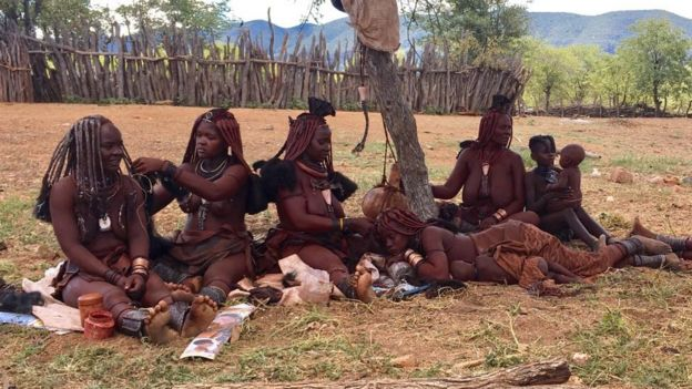 Himba women doing their hair in Omuhoro village, Kunene region, Namibia