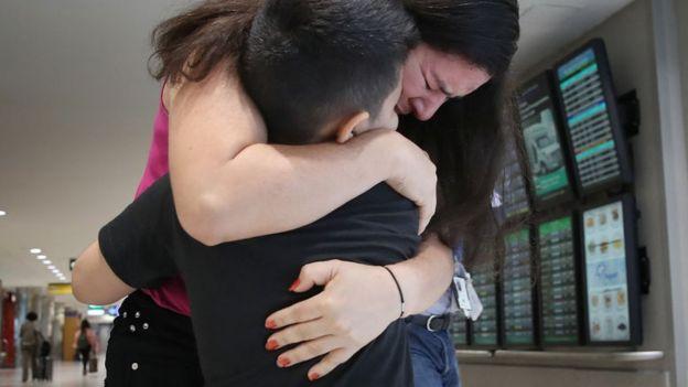 Una madre migrante reunida con su hijo en un aeropuerto de EE.UU.