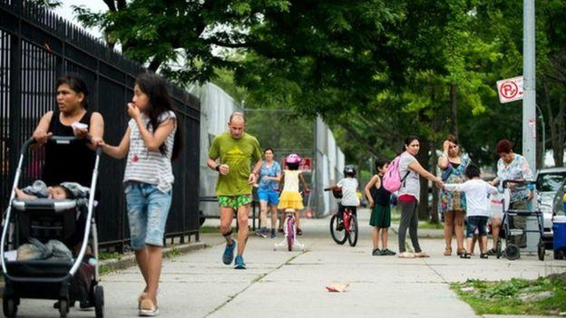 Un competidor y peatones en la acera
