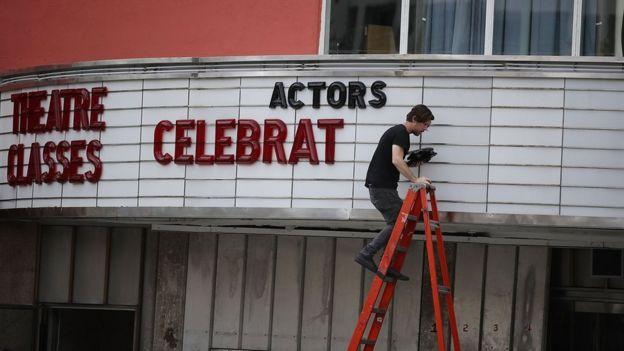 Un hombre saca las letras de la marquesina de un teatro en Coral Gables.