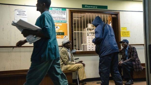 Men wait for medicines at a pharmacy at Parirenyatwa Hospital in Harare, September 2019