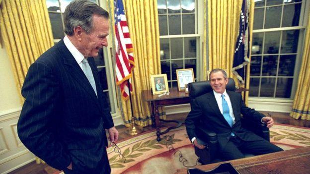 """2001年1月20日,小布什首次就职典礼日,他坐在椭圆形办公室内""""接见""""父亲"""