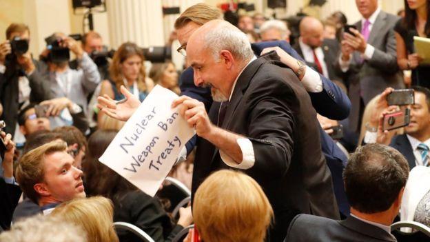 "Periodista con un letrero que dice ""Tratado de prohibición de armas nucleares""."