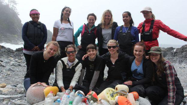 Mujeres participantes de EXXpedition en una playa frente a una pila de plástico que recogieron