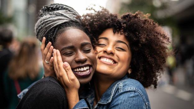Dos mujeres jóvenes sonríen y se abrazan en la calle.