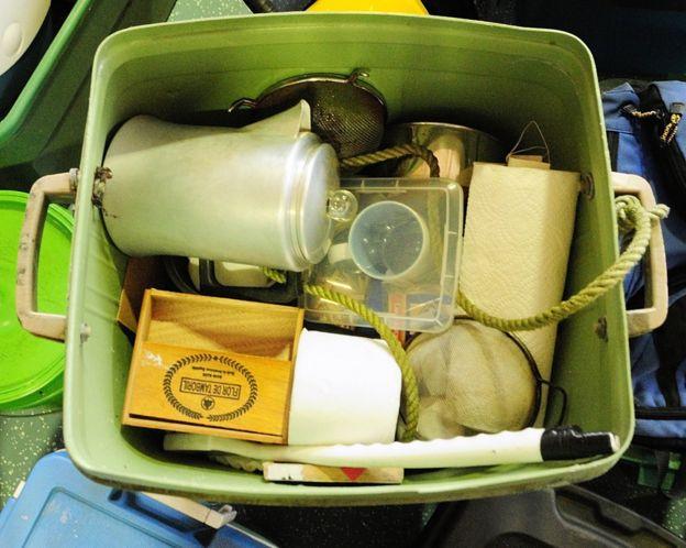 Uma caixa com uma cafeteira e vários itens de uso pessoal de Knight