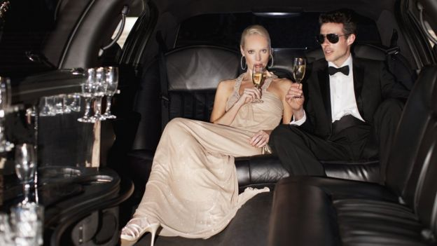 Casal bebe champanhe dentro de limousine