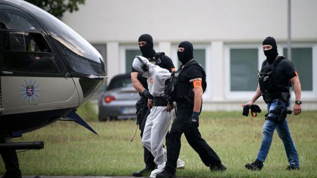Police officers of a special unit escort Iraqi asylum seeker Ali Bashar, who is suspected of having killed a German teenage girl, to a helicopter in Wiesbaden, western Germany, on June 10, 2018