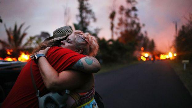 Dos personas se consuelan en un abrazo mientras a lo lejo se ve la erupción del volcán