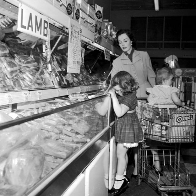 A mother and her two children shopping in a supermarket in the 1950s