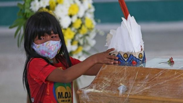 Indigenous child wearing mask puts headdress on coffin in Brazil