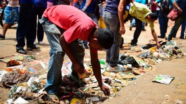 Un muchacho busca comida a las afueras de un supermercado saqueado en Caracas en abril de 2017. Foto: AFP
