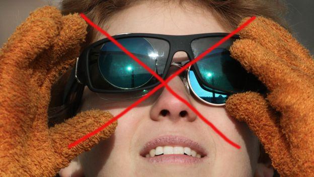 Joven con dos pares de lentes comunes de sol