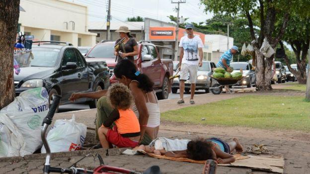 Imigrantes venezuelanos pedindo ajuda no semáforo