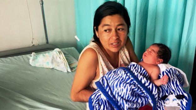 Mulher com o bebê em cama de hospital