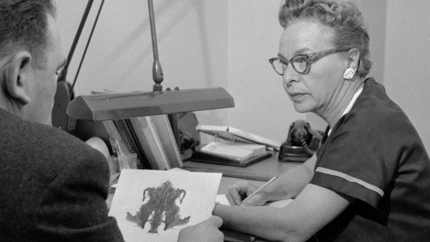 Psicóloga realizando a un sujeto la prueba de la mancha de tinta