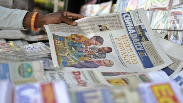 A newspaper vendor arranges copies of China's Africa edition of its daily newspaper