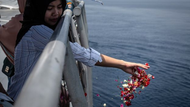 A family of one of the victims of Lion Air flight JT 610 throws flowers on deck of the Indonesian Navy ship, 6 November 2018