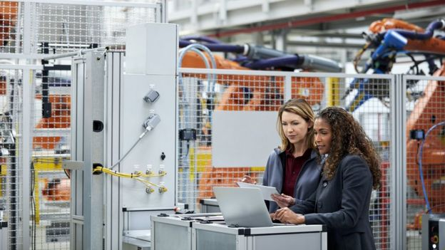 Female workers in a car factory discussing technological solutions