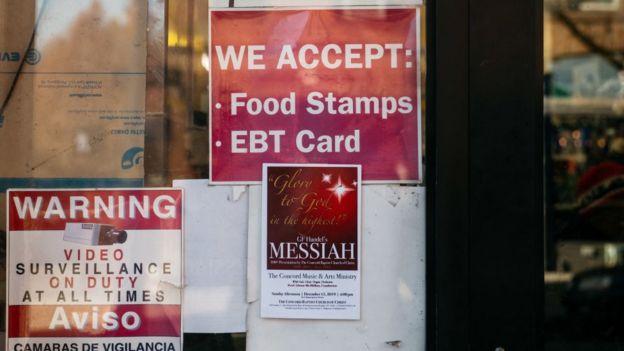 """Un negocio con un cartel en el que se informa que aceptan """"food stamps"""" como forma de pago."""