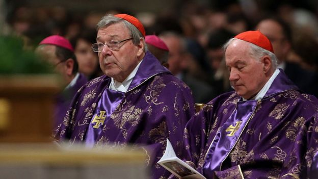 Cardinal George Pell (l) listens to a mass, while sitting among other cardinals at St Peter's Basilica on February 10, 2016 in Vatican City
