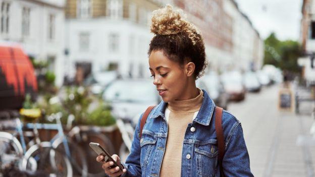 Mujer mirando su móvil en la calle.