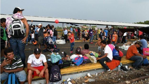 Migrantes esperan en el puente fronterizo entre Guatemala y México.