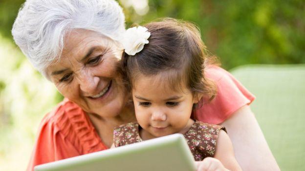 Una abuela con su nieta mirando una tableta.