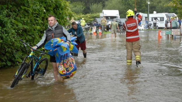 Firefighters help campers, carrying bikes from their motorhomes in Pembrokeshire