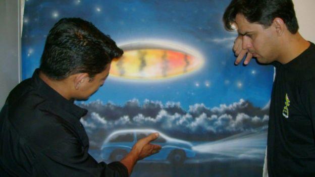 O jornalista Genito mostra um quadro que pintou, baseado na experiência que relata ter tido com óvnis - no quadro, uma nave oval brilhante sobrevoa um carro