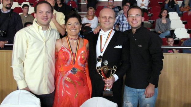 Florin and Mariuca Talpes celebrating winning a ballroom dancing trophy with their sons
