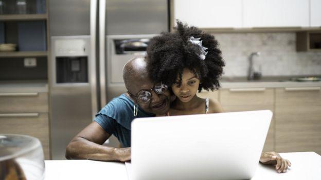 Una niña con su abuela y una computadora.
