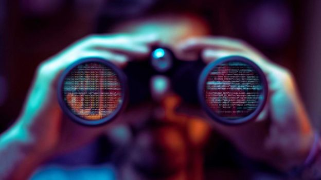 Un hombre mirando por unos binoculares, en cuyas lentes se ven reflejados códigos de computación