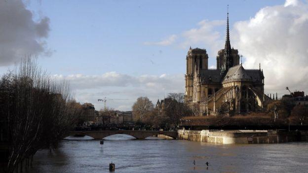 Ile de la Cite and Notre-Dame cathedral with the River Seine rising as it flows under the Pont de l'Archevêché, 26 Jan 2018