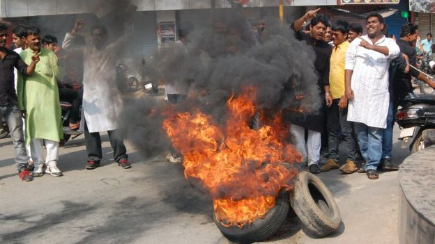 Hombres manifestándose con llantas quemadas en la calle.