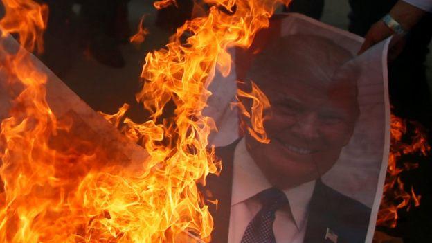 Palestinos en Gaza queman un afiche con la foto de Donald Trump