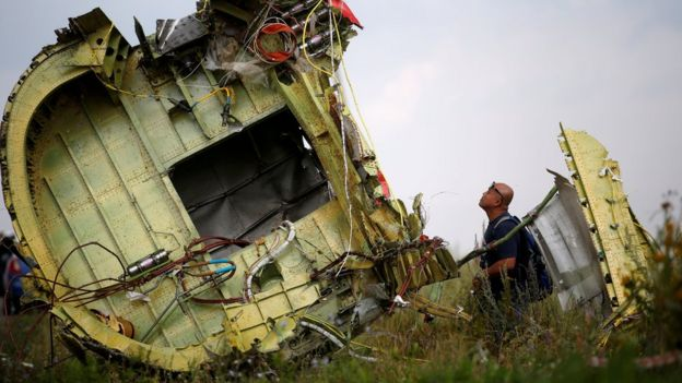 An investigator inspects the wreckage of flight MH17