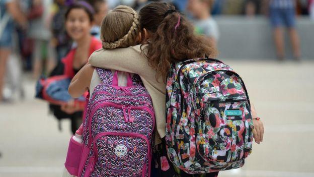 Meninas de costas, usando mochilas