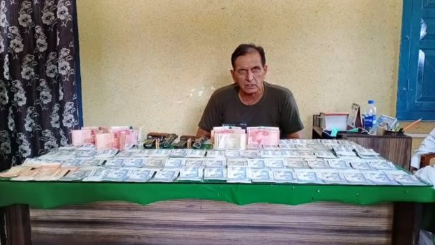 The head of the local police force with the cash seized at the race