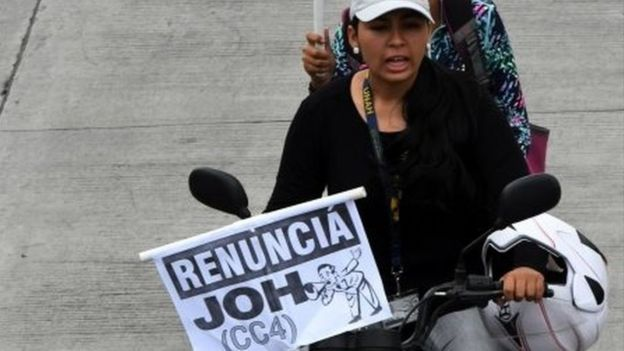 """Protesters on a motorbike hold up placards reading """"resign JOH (CC4)"""