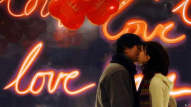 Namorados se beijam em frente a um letreiro luminoso